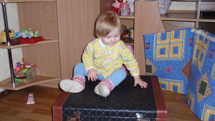 маленький ребенок изучает старый чемодан